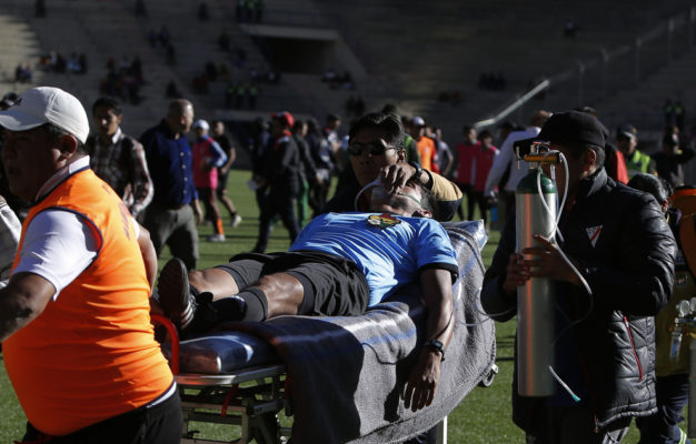 """Referee Victor Hugo Hurtado is transported off the field to the hospital after fainting during a soccer game between the Always Ready team and Oriente Petrolero team, part of the """"Apertura"""" local soccer tournament in El Alto, Bolivia, Sunday, May 19, 2019. Hurtado, 31, died later at the hospital of cardiac arrest, according to Fernando Costa, president of the Always Ready soccer club. (AP Photo/Juan Carlos Usnayo)"""