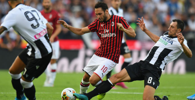 UDINE, ITALY - AUGUST 25: Hakan Calhanoglu of AC MIlan competes for the ball with Mato Jajalo of Udinese Calcio during the Serie A match between Udinese Calcio and AC Milan at Stadio Friuli on August 25, 2019 in Udine, Italy. (Photo by Alessandro Sabattini/Getty Images)